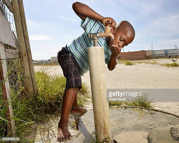 Young boy drinking water from a communal township tap. Mfuleni, Cape Town, South Africa.