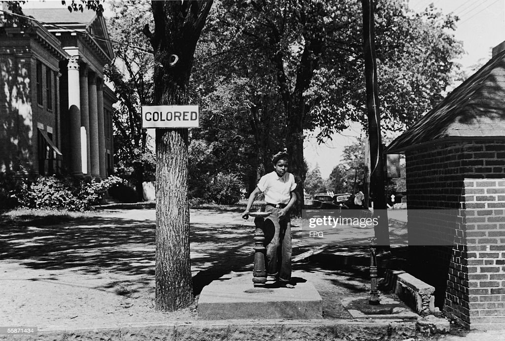 A young boy drinks from the 'colored' water fountain on the county courthouse lawn Hallifax North Carolina April 1938
