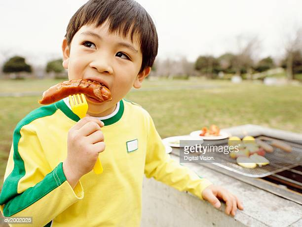 Young Boy Eating a Sausage