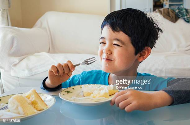 Young boy eating a slice of cake