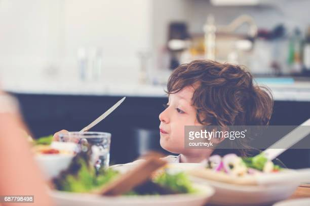 Young boy eating at the table.