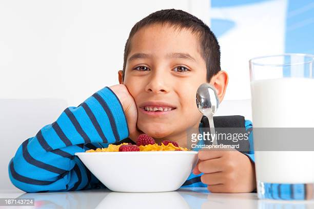 Young boy eating breakfast before heading to school