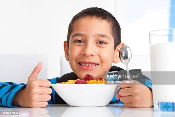 Jeune garçon manger le petit déjeuner avant de vous rendre à l'école
