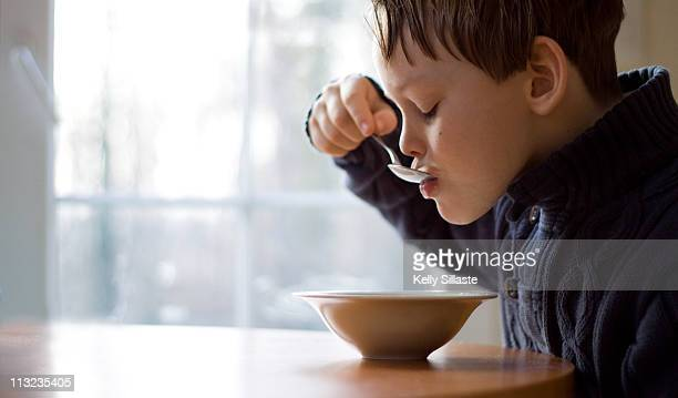 Young boy eating cereal for breakfast