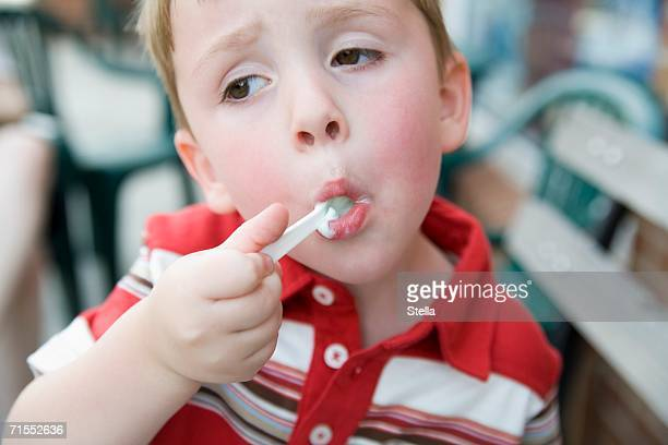 Young boy eating ice cream with spoon
