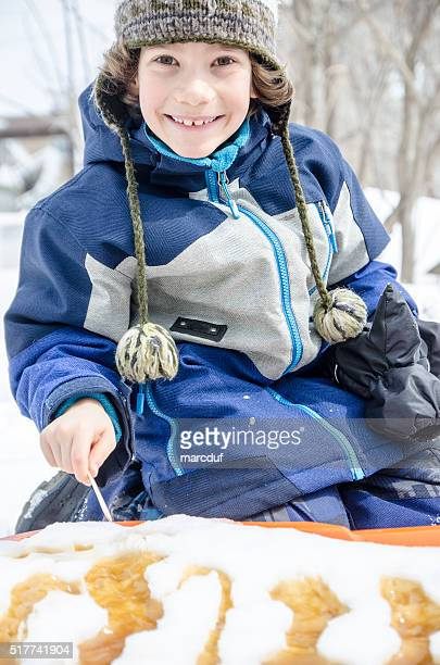 Young boy eating maple syrup taffy outside