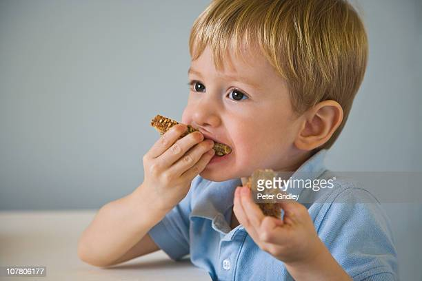 Young boy eating multigrain bread with nut butter