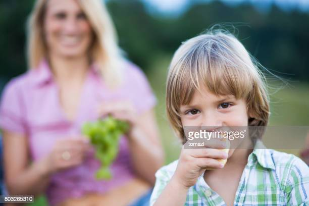 Young boy eating on a family picnic