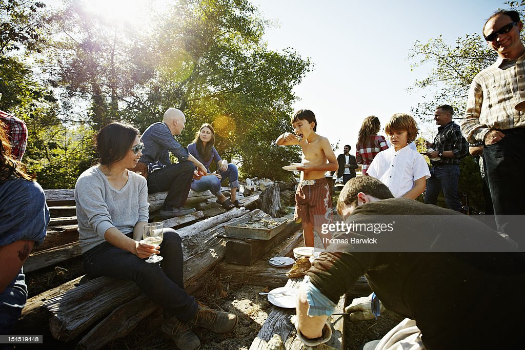 Young boy eating oyster with friends and family