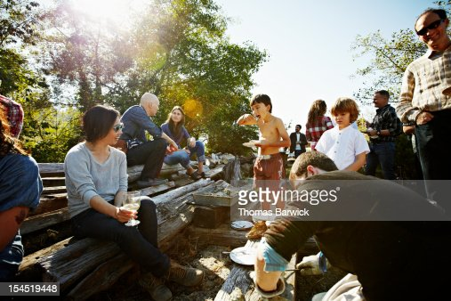 Young boy eating oyster with friends and family : Stock Photo