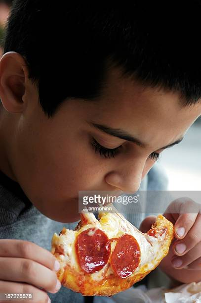 Young boy eating pepperoni pizza