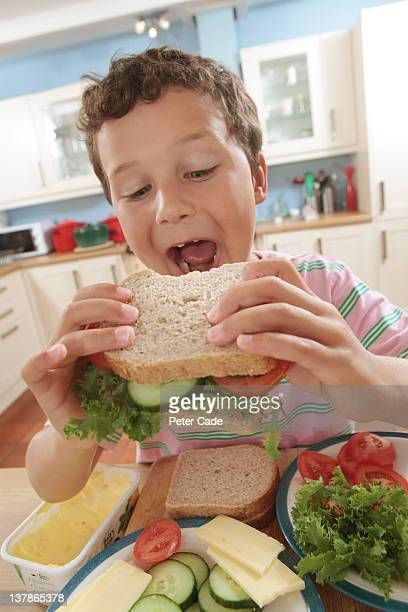 young boy eating sandwich he has made