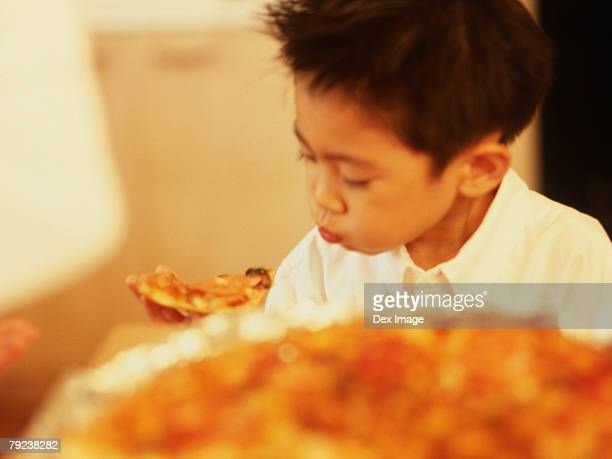Young boy eating slice of pizza