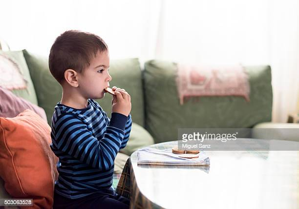 young boy eating sweets at breakfast
