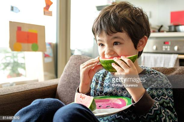 Young boy eating water melon