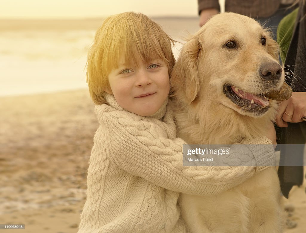 Young boy embracing dog. Beach : Stock Photo