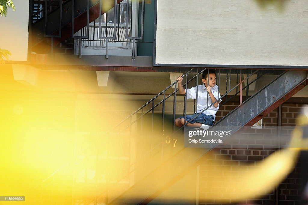 A young boy escapes the heat of his apartment after the air conditioning and electricity in the area was cut off by law enforcement agents and explosives experts trying to enter and render safe James Holmes' apartment July 21, 2012 in Aurora, Colorado. According to police in Aurora, a suburb of Denver, Holmes, 24, is in custody and is suspected of killing 12 people and injuring 59 during a screening of 'The Dark Knight Rises.' Holmes left his apartment filled with 30 various devices and trip wires meant to kill or hurt anyone entering.
