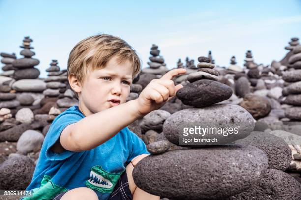 Young boy examining stack of rocks, Santa Cruz de Tenerife, Canary Islands, Spain, Europe