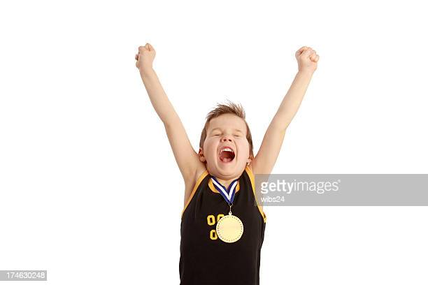 A young boy excited about winning a medal