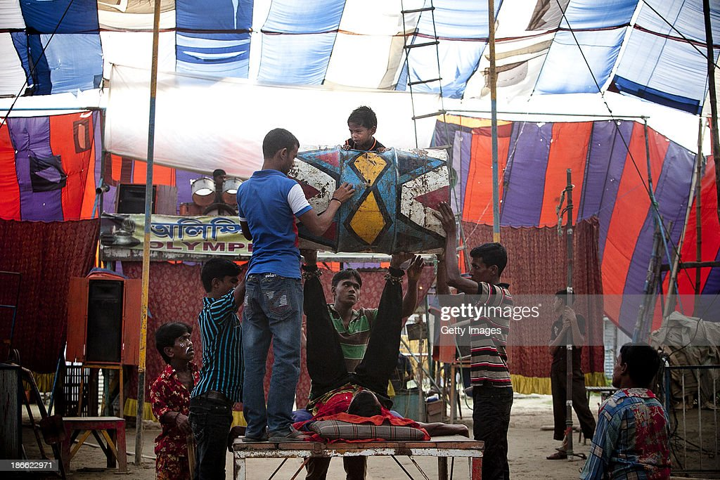A young boy exits a drum during a presentation at the Olympic Circus, November 1, 2013 in Jamsha, Bangladesh. Generations of low income families are born into circuses with rarely the hope of ever working in different profession or escaping the harsh realities of the circus. The children, often very young, are trained to be full working members usually without the opportunity for an education. As modernization slowly takes over landscape of Bangladesh, the circus is a dying art form and is moving further and further away from mainstream entertainment.