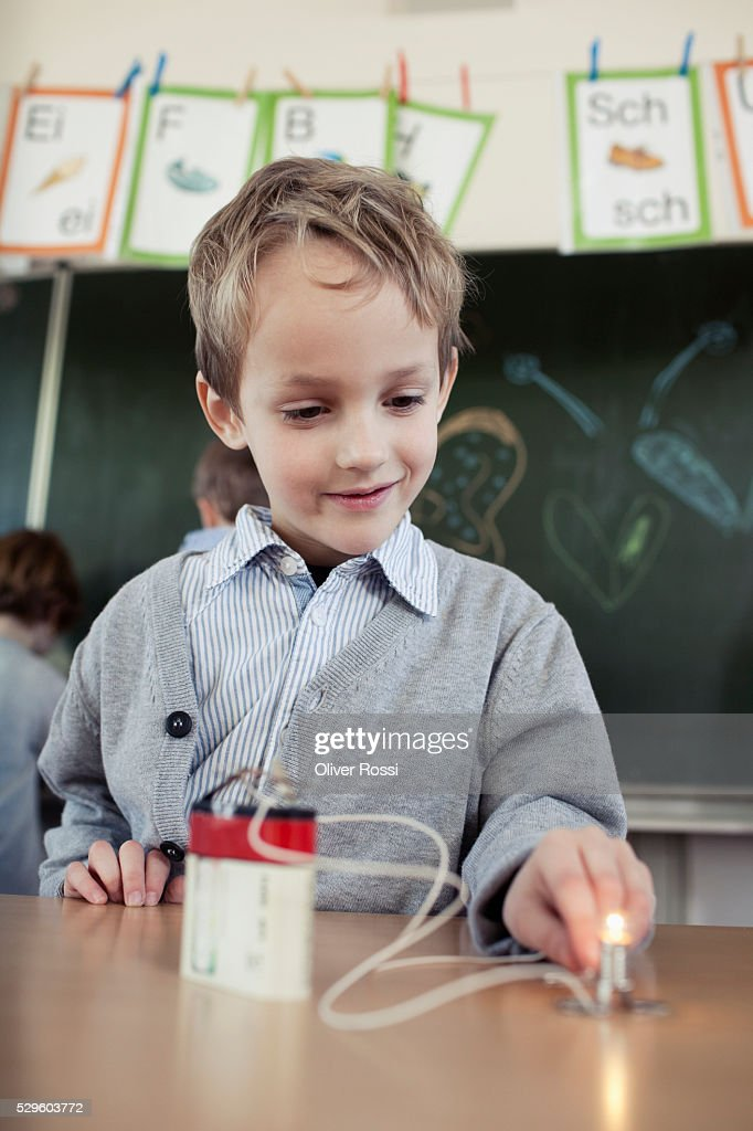 Young boy (6-7) experimenting with electricity in science class : Foto de stock