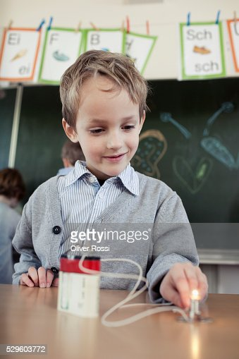 Young boy (6-7) experimenting with electricity in science class : Stock Photo