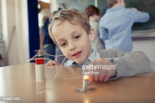 Young boy (6-7) experimenting with electricity in science class : Stock-Foto