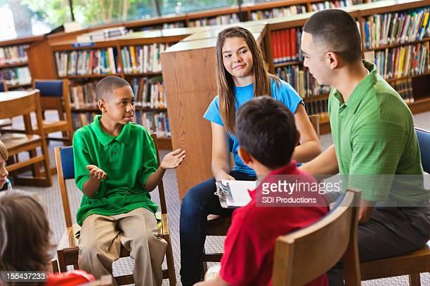 Young boy explicando algo de clase en la escuela de la biblioteca