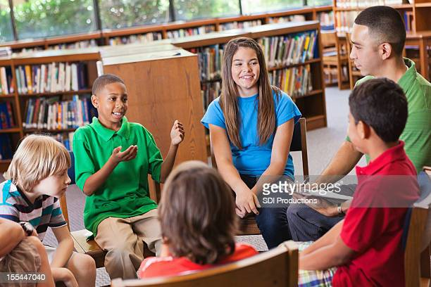 Young boy explaining something to classmates in the school library