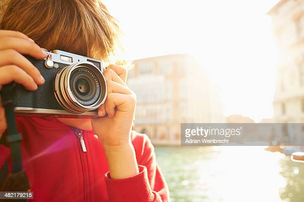 Young boy exploring with camera, Venice, Italy