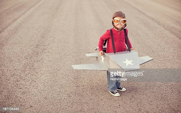 Young boy flying a cardboard airplane