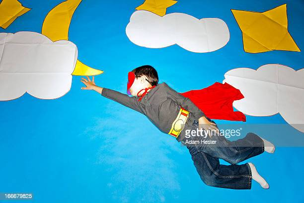 A young boy flying on blue paper with clouds