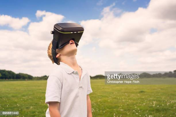 Young boy gazing up while using VR headset