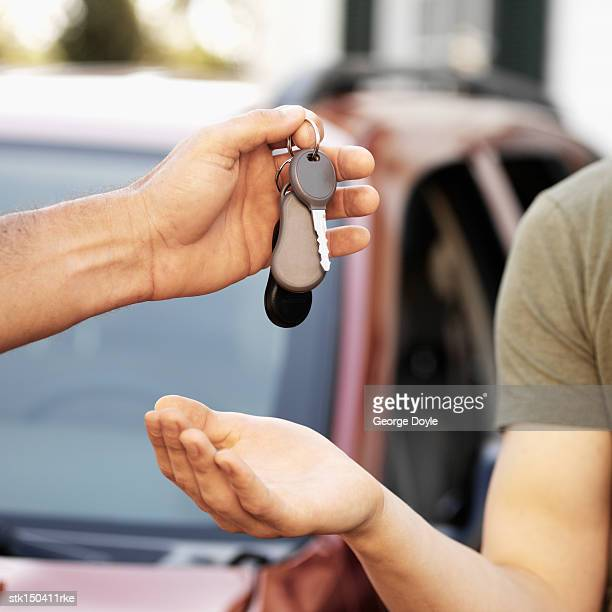 Young boy getting keys from a man