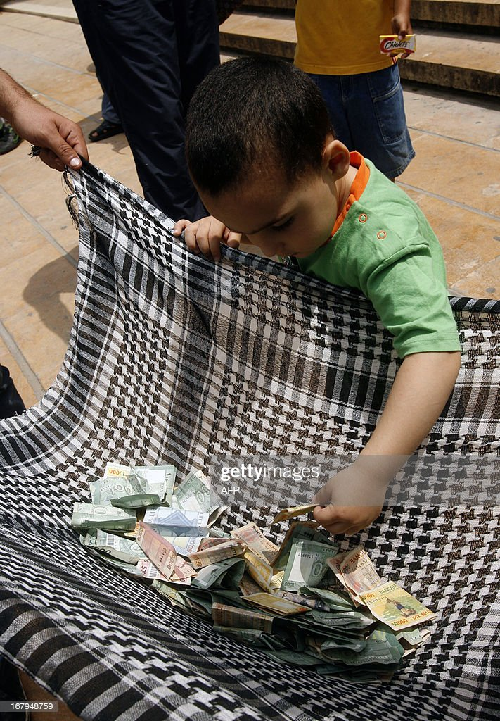 A young boy gives a note to members of the Islamic Group, Jamaa Islamiya, who collect money outside a mosque after the Friday prayers in order to 'help free Syrian Revolutionists', as mentioned in their statement on May 3, 2013 in the southern Lebanese city of Sidon.