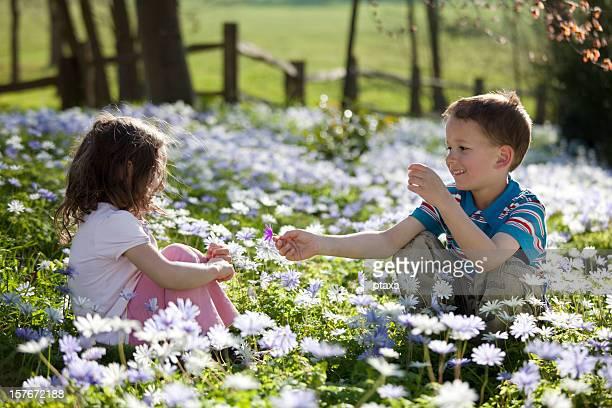 Garçon fille donnant une fleur