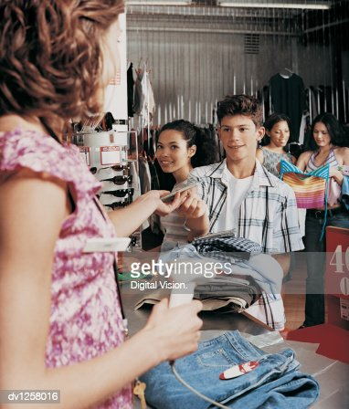 young boy giving a shop assistant a music cd over the checkout    young boy giving a shop assistant a music cd over the checkout counter in a clothes shop