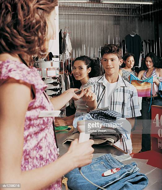 Young Boy Giving a Shop Assistant a Music Cd Over the Checkout Counter in a Clothes Shop