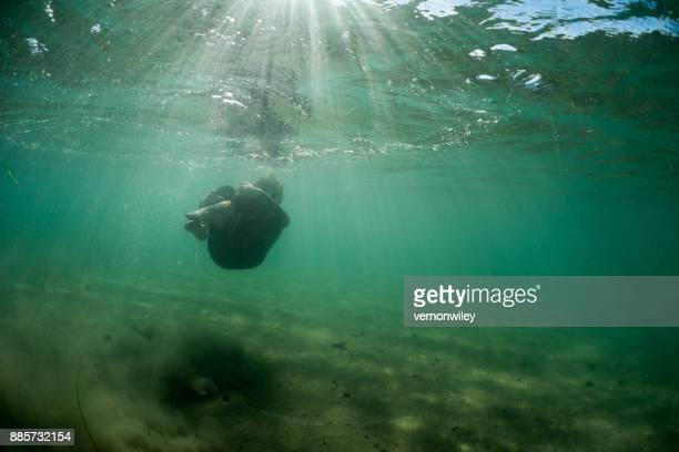 Young boy grieves underwater in a protective ball