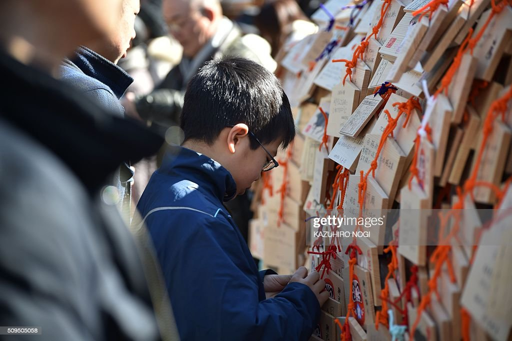 A young boy hangs a small wooden votive tablet after writing his wishes on it, at Yushima Tenjin shrine in Tokyo on February 11, 2016. Every year many students and their parents come to the shrine to pray for success at exam time as the annual school entrance examination season started. AFP PHOTO / KAZUHIRO NOGI / AFP / KAZUHIRO NOGI