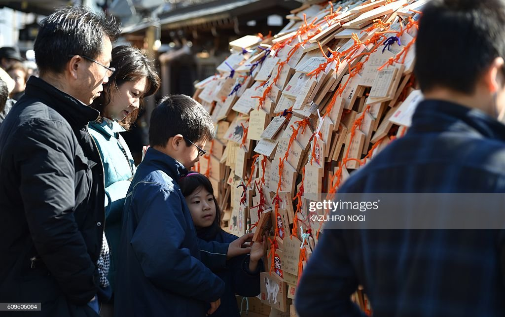 A young boy (3rd L) hangs a small wooden votive tablet after writing his wishes on it, at Yushima Tenjin shrine in Tokyo on February 11, 2016. Every year many students and their parents come to the shrine to pray for success at exam time as the annual school entrance examination season started. AFP PHOTO / KAZUHIRO NOGI / AFP / KAZUHIRO NOGI
