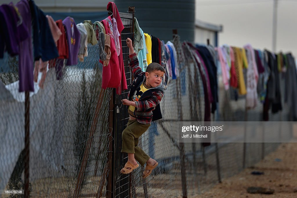 ZA'ATARI, JORDAN - FEBRUARY 01: Young boy hangs on a fence with clothing hung from it, as Syrian refugees go about their daily business in the Za'atari refugee camp on February 1, 2013 in Za'atari, Jordan. Record numbers of refugees are fleeing the violence and bombings in Syria to cross the borders to safety in northern Jordan and overwhelming the Za'atari camp. The Jordanian government are appealing for help with the influx of refugees as they struggle to cope with the sheer numbers arriving in the country.