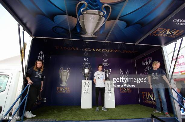 A young boy has his picture taken by the Champions League and Women's Champions League trophies on display outside the stadium prior to the Premier...
