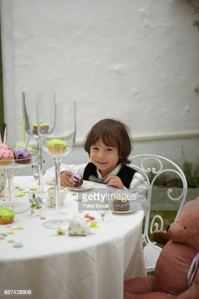 Young boy having a tea party with stuffed bear