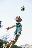 young boy heading a soccer ball