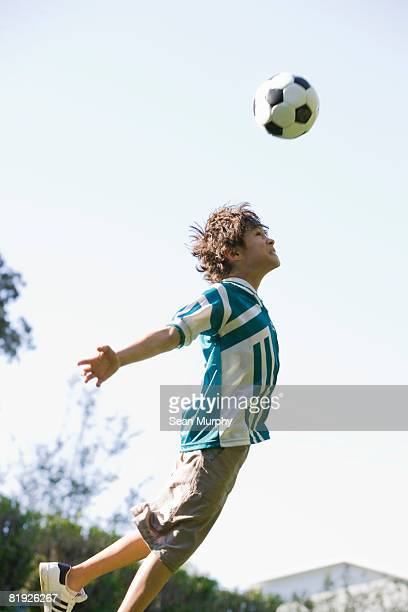 young boy heading a soccer ball
