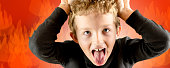 closeup of young boy heavy screaming expression with crazy look and frenzy in his eyes, very angry expression on red fire background