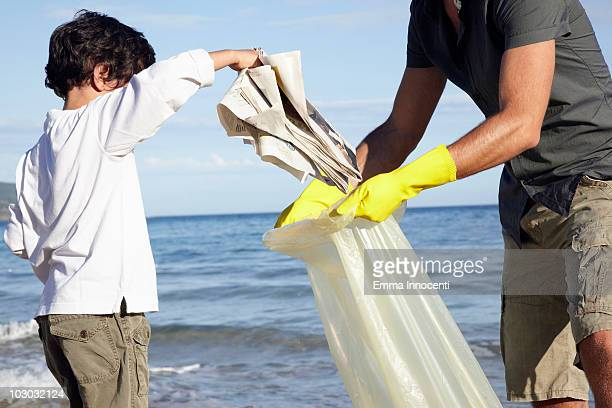 Young boy helping dad cleaning beach