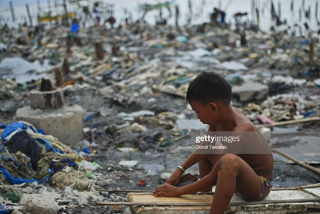A young boy helps in rebuilding what's left of a shanty on the coastal community of Navotas town on October 6, 2011 in Manila, Philippines. The rebuilding of coastal communities along Manila have begun even as city government officials are contemplating relocating informal settlers living along manila's coast to prevent future calamities in coastal areas of the city. Water levels have slowly receded in the wake of typhoons Nalgae and Nesat that have left nearly 60 dead and millions affected.