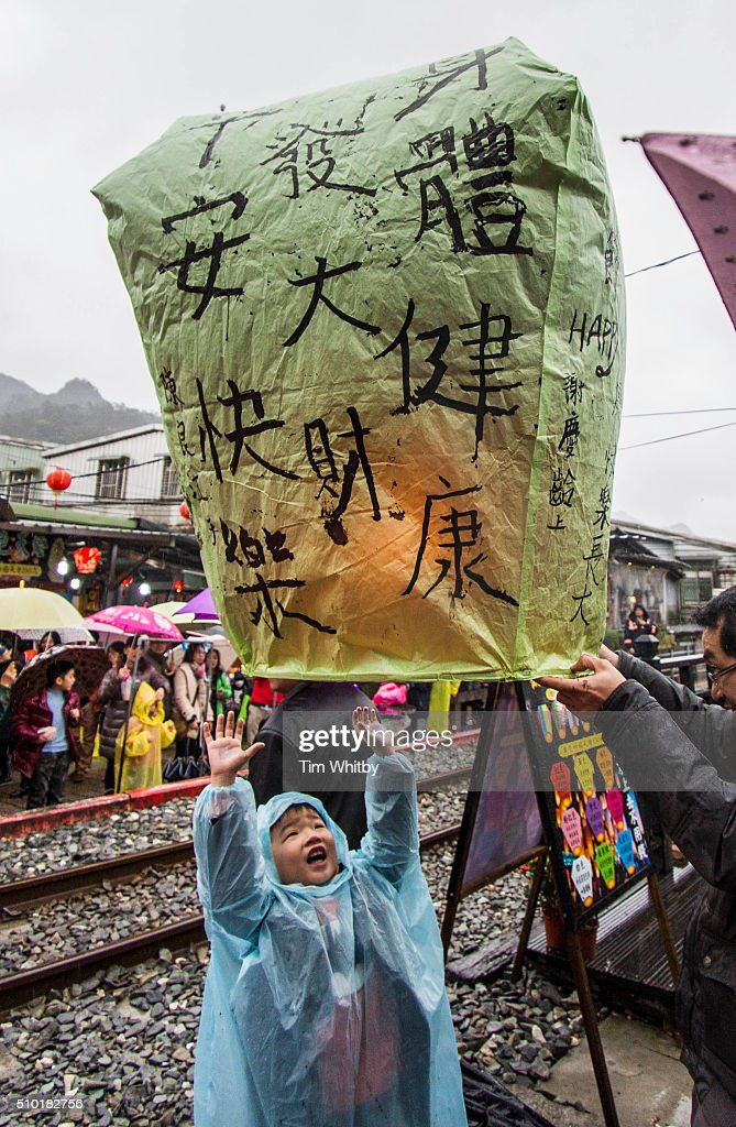 A young boy helps to launch a lantern at the Pingxi Sky Lantern Festival on February 14, 2016 in Pingxi District, New Taipei City, Taiwan. The event is the second of three organised lantern releases and the theme for the launch is 'Two Hearts Together'. Participants were encouraged to 'leave their love in Pingxi' and draw hearts on their lanterns.